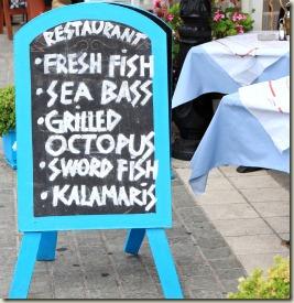 Menu board outside of a fish restaurant in Greece
